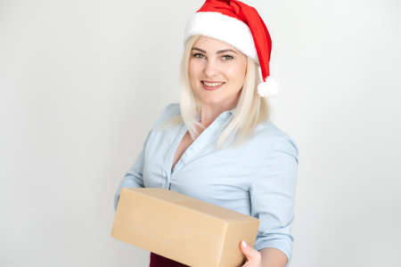New Years Christmas parcels in recognizable boxes, delivery online store, a pretty woman in a red Santa Claus hat holds a stack of boxes. Isolated on a white.
