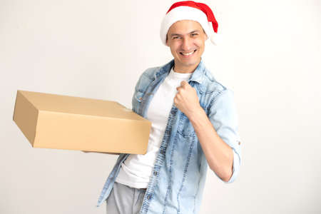 Laughing delivery man in santa claus hat on the phone, standing and holding carton box on one hand. isolated on white.