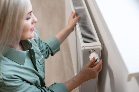 Young and beautiful blond woman touching the radiator. Heating season concept. Standard-Bild
