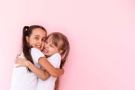 Two little girls hugging each other. Isolated on on a pink background