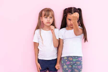 Image of two angry teenage girls with braids in casual clothes standing isolated over pink background