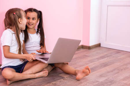 Two little girls sitting in front of a laptop and laughing, close-up, positive emotions, entertainment on the Internet for children