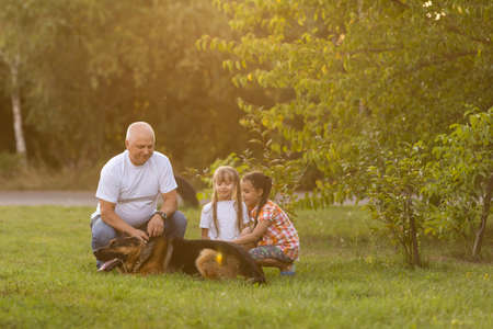 Grandfather And Granddaughters Taking Dog For Walk Stock Photo