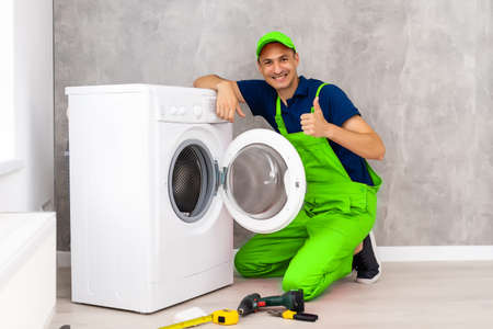 male adult repairman with tool and clipboard checking washing machine in bathroom
