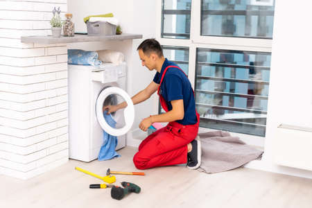 Plumber in overalls with tools is repairing a washing machine in the house