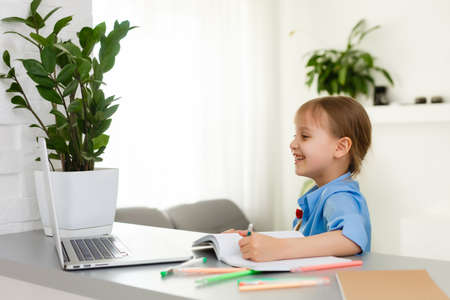 Smart Little Girl Does Homework in Her Living Room. Shes Sitting at Her Desk Writes with a Pen in Her Textbooks and Uses Laptop. Stock Photo