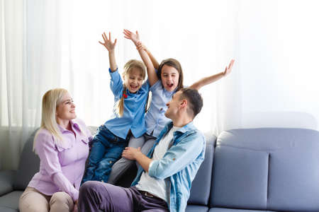 Cheerful young family with kids laughing sitting on couch together, parents with children enjoying entertaining at home