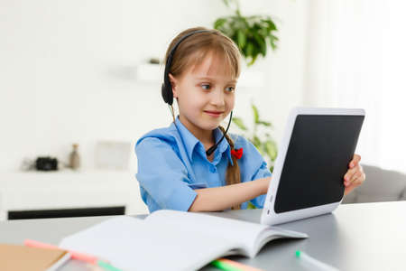 Remote lessons. The child smiles happily and gets knowledge remotely. Little girl study online learning from home. Online school.