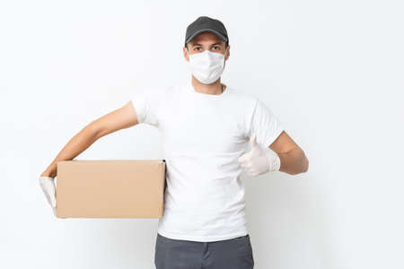 Courier, delivery man in medical latex gloves and mask safely delivers online purchases in white box to the door during the epidemic. Stay home, safe concept.