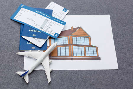 Flight tickets with passports, model of airplane and map on gray background.