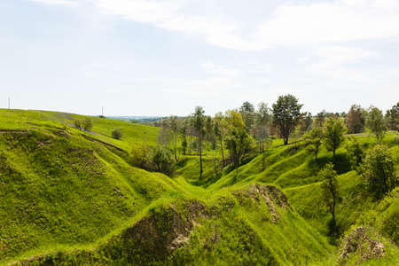 Spring photography, meadows, fields, ravines, hills, rural landscape. A deep, narrow gorge with steep slopes. A naturally raised area of land, not as high or craggy as a mountain.