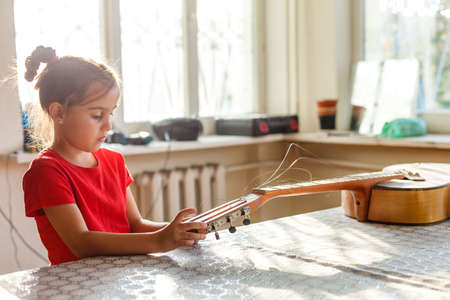 little girl holding a broken guitar, guitar repair