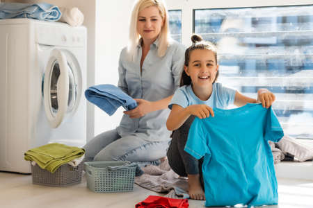 Happy housewife and her daughter with linen near washing machine Stock Photo