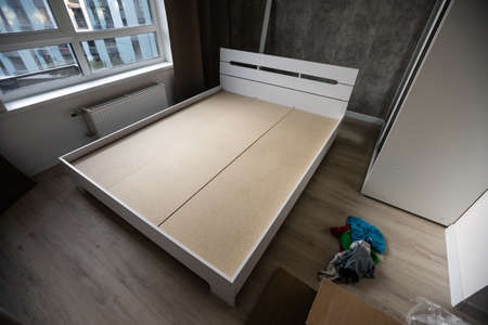 assembly of a double bed made of wood and lamella