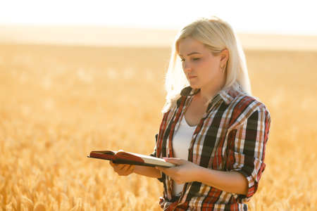 Woman holding a Bible, a natural field.