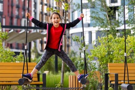 Child on monkey bars. Kid at school playground. Little girl hanging on gym activity center of preschool play ground. Healthy outdoor activity for kids. Sport for young children.