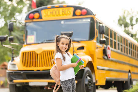Girl with backpack near yellow school bus. Transport for students
