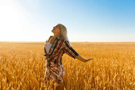 A girl in the midst of wheat spikelets. Caucasian woman posing with spikelets outside.