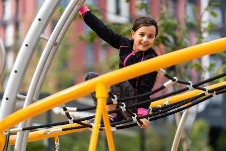 Little girl having fun playing on the sports ground Zdjęcie Seryjne