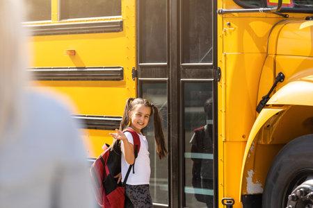 Mother brings her daughter to school near the school bus. back to school Reklamní fotografie