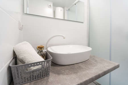Detail of counter top washbasin in modern bathroom with accessories of steel and vase