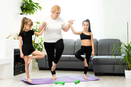 adult woman with her granddaughters. Morning exercises, yoga - do at home all together. Grandmother and granddaughters doing yoga exercise home. Mother and daughter do gymnastics exercises. Imagens