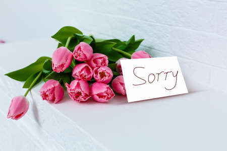 word SORRY and bouquet of tulips