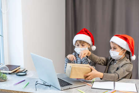 Christmas greetings online. two little girls in medical masks a laptop. Shows gifts, online purchases to the camera. Greeting video calls to friends, relatives and parents