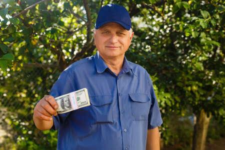 Cheerful senior holding money bundles in the garden background