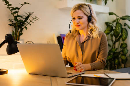 Woman having video chat with colleagues at laptop in office, closeup