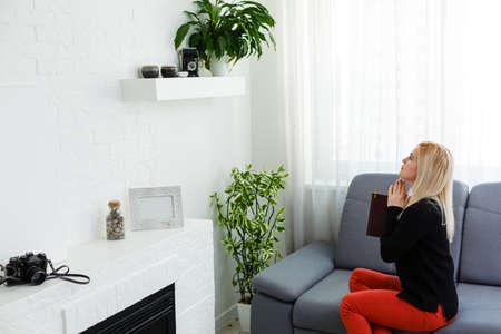 Girl praying. beautiful young blond hair woman praying at home