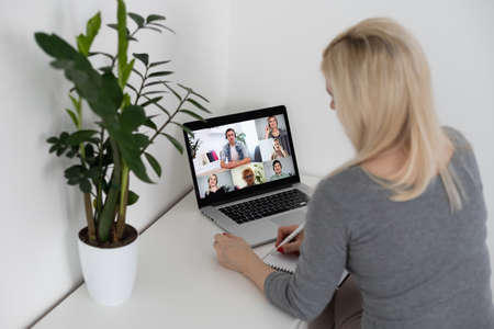 Back view of business woman talking to her colleagues about plan in video conference. business team using laptop for a online meeting in video call. Group of people smart working from home.