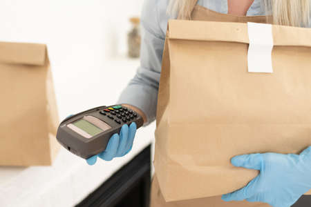 woman with pos terminal and delivery package