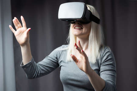 Attractive young woman adjusting her VR headset and smiling