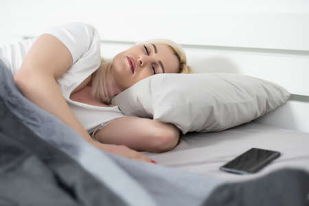 Morning with gadget. Overhead of beautiful young woman lying on the bed, smartphone. Banque d'images