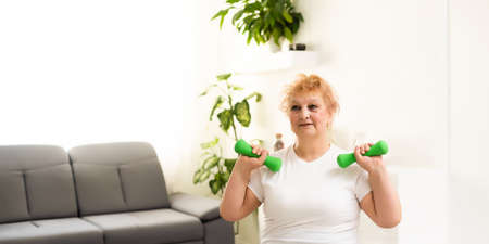 Gym At Home. Positive Aged Woman Training With Dumbbells In Living Room, Copy Space