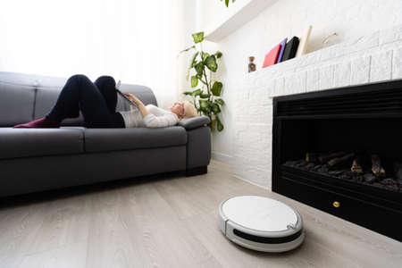 Robotic vacuum cleaner cleaning the room while woman relaxing on sofa. Woman controlling vacuum with remote control
