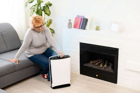 an elderly woman uses an air purifier in an apartment while dust air pollution situation outside Фото со стока