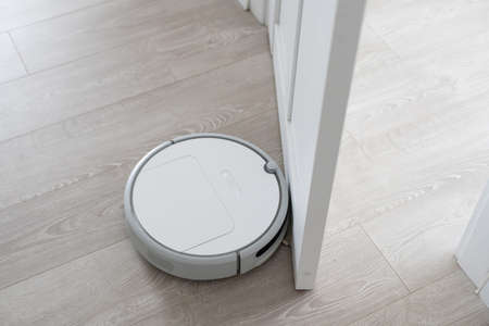 White robotic vacuum cleaner on laminate floor cleaning dust in living room interior. Smart housekeeping technology.