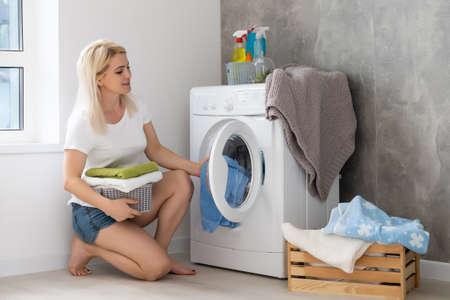 pretty smiling girl in the laundry room Foto de archivo