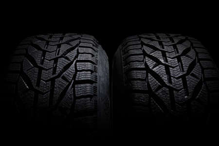 Closeup car tire isolated on black background. Wet with drops wheel against black
