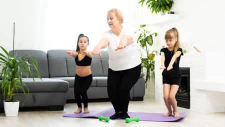 grandmother and children exercising workout at home near the window in room