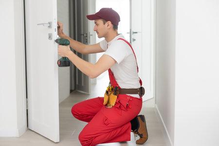 The master worker installs a door lock in the front door, metal doors with a polymer coating