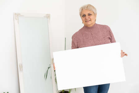 elderly woman holds a photo canvas