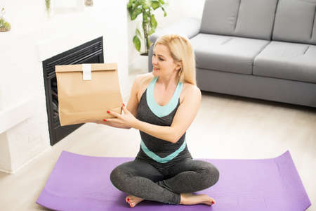 sportive woman next to delivery packages with healthy food