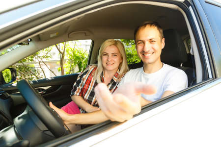 Happy young man and woman in a car enjoying a road trip on a summer day.