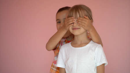 Portrait of two cute friends 7 years old girl Covering Eyes Isolated over pink background