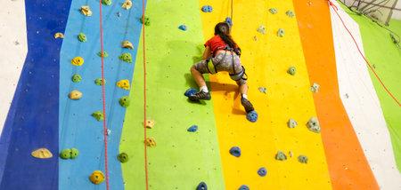 Sporty little girl climbing artificial boulder on practical wall in gym Reklamní fotografie