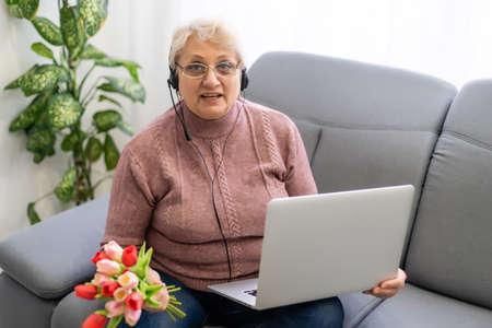 Cropped shot of a beautiful elderly woman using laptop computer while sitting with flowers