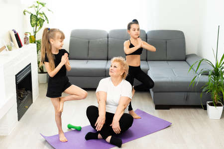 adult woman with her granddaughters. Morning exercises, yoga - do at home all together. Grandmother and granddaughters doing yoga exercise home. Mother and daughter do gymnastics exercises.